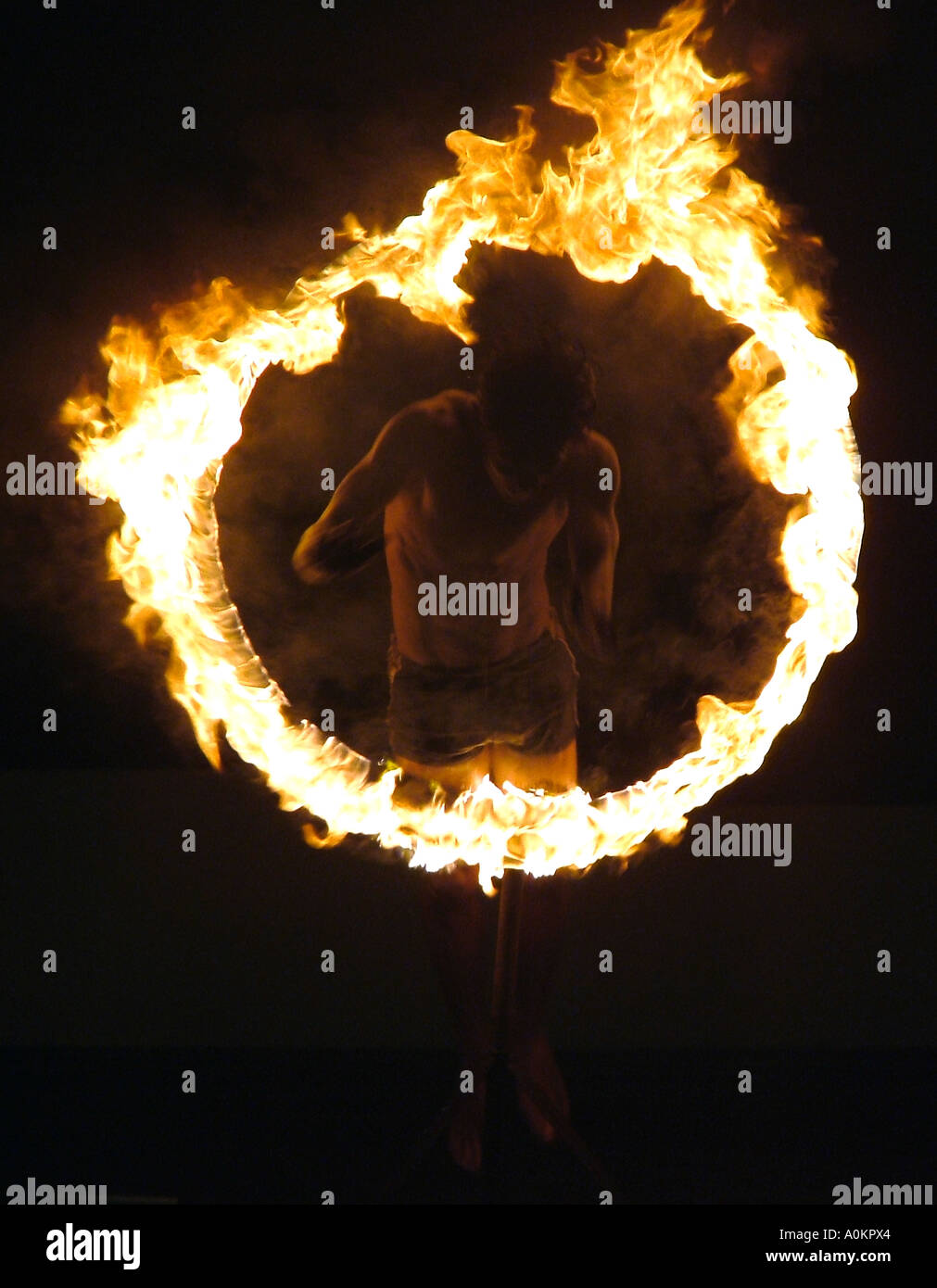 A ghostly image of a local Sri Lankan performer jumping through a blazing fire hoop in the darkness. - Stock Image