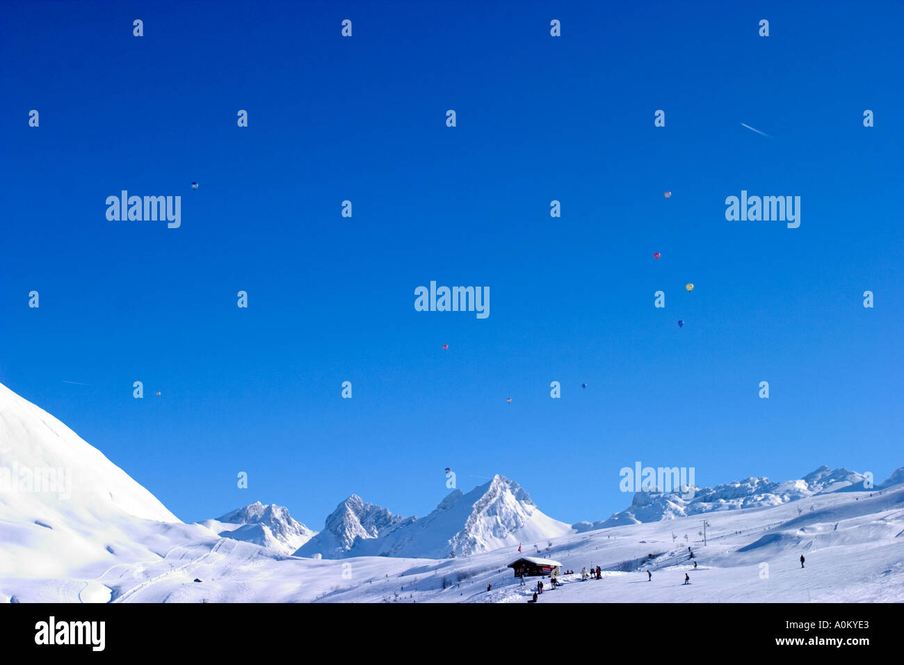 Skiers on chair lift and general view of ski station of grand bornand haute savoie 74 france - Stock Image
