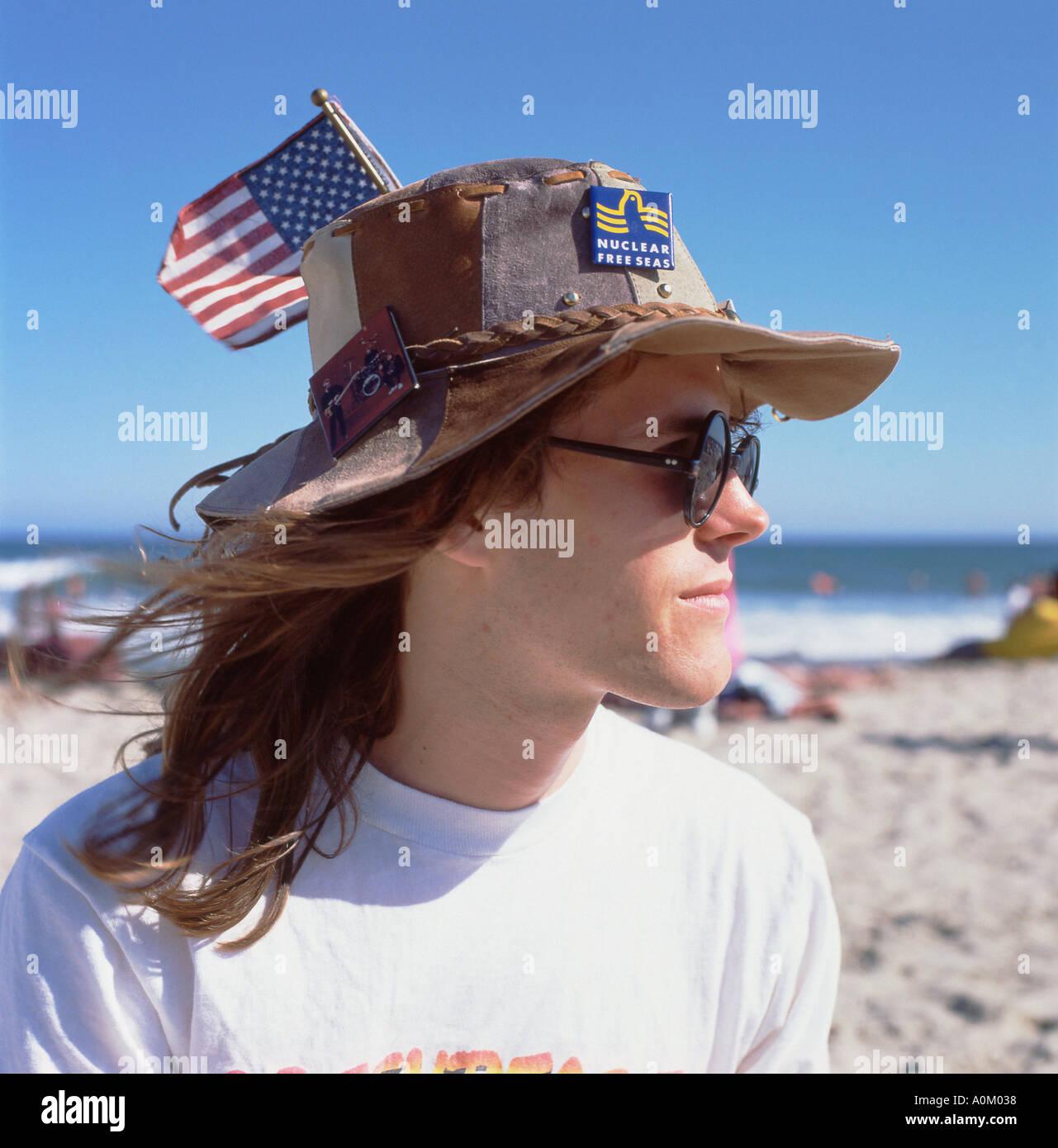 A young man wearing Greenpeace nuclear free seas badge and an American flag on his hat Malibu LA California USA    KATHY DEWITT - Stock Image