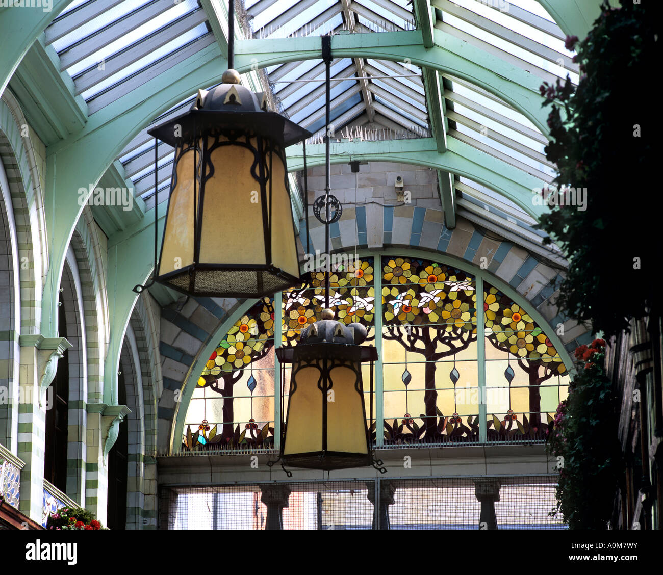 Art Nouveau lamp shades and stained glass window inside the Royal Arcade, Norwich city centre, Norfolk. Stock Photo