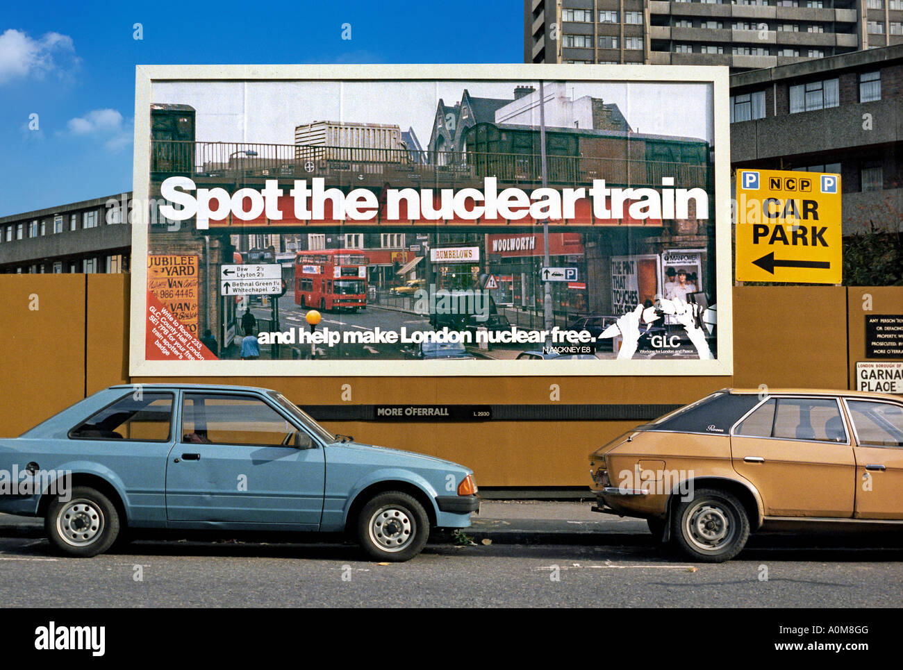 A GLC 'Spot the Nuclear Train' poster on a billboard in south London, 1983. The poster shows Mare St. Hackney. - Stock Image