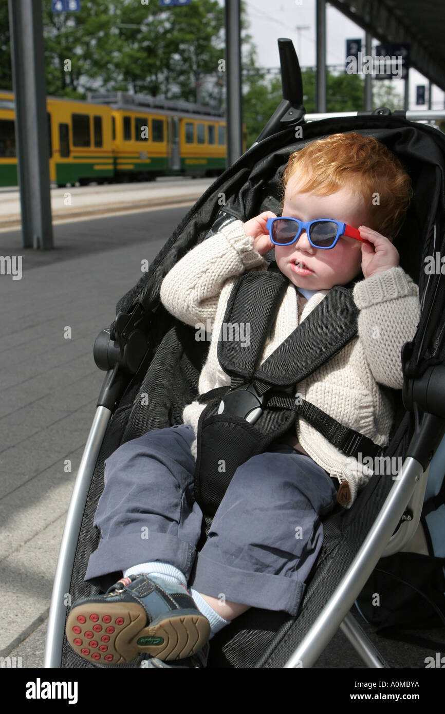 little baby boy in pushchair with funny sunglass - Stock Image