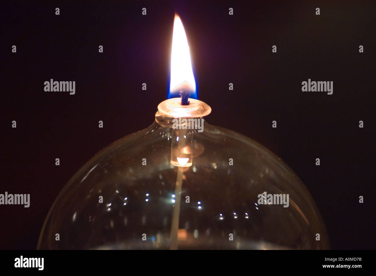 A flame burning on a glass globe oil lamp - Stock Image
