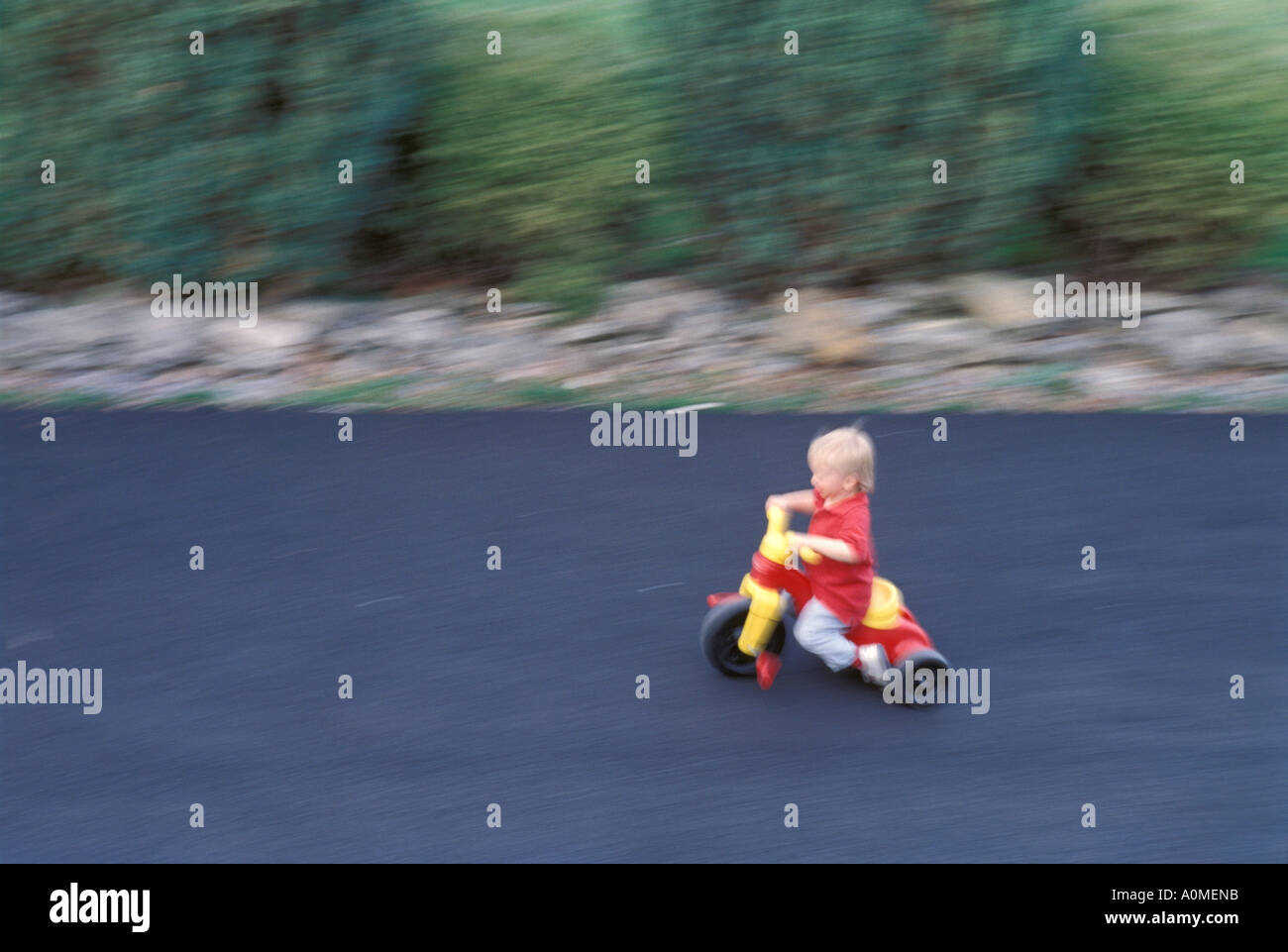 1 one young boy male blonde cute red jacket toddler 2 years old summer  tricycle movement motion blur