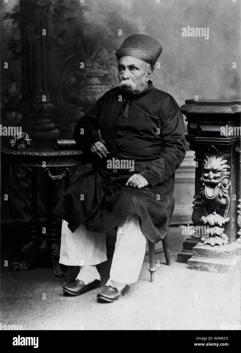 CMP 92051 Old Historical Picture of one old man dressed in Parsi suit with piajama sitting on a chair India - Stock Image