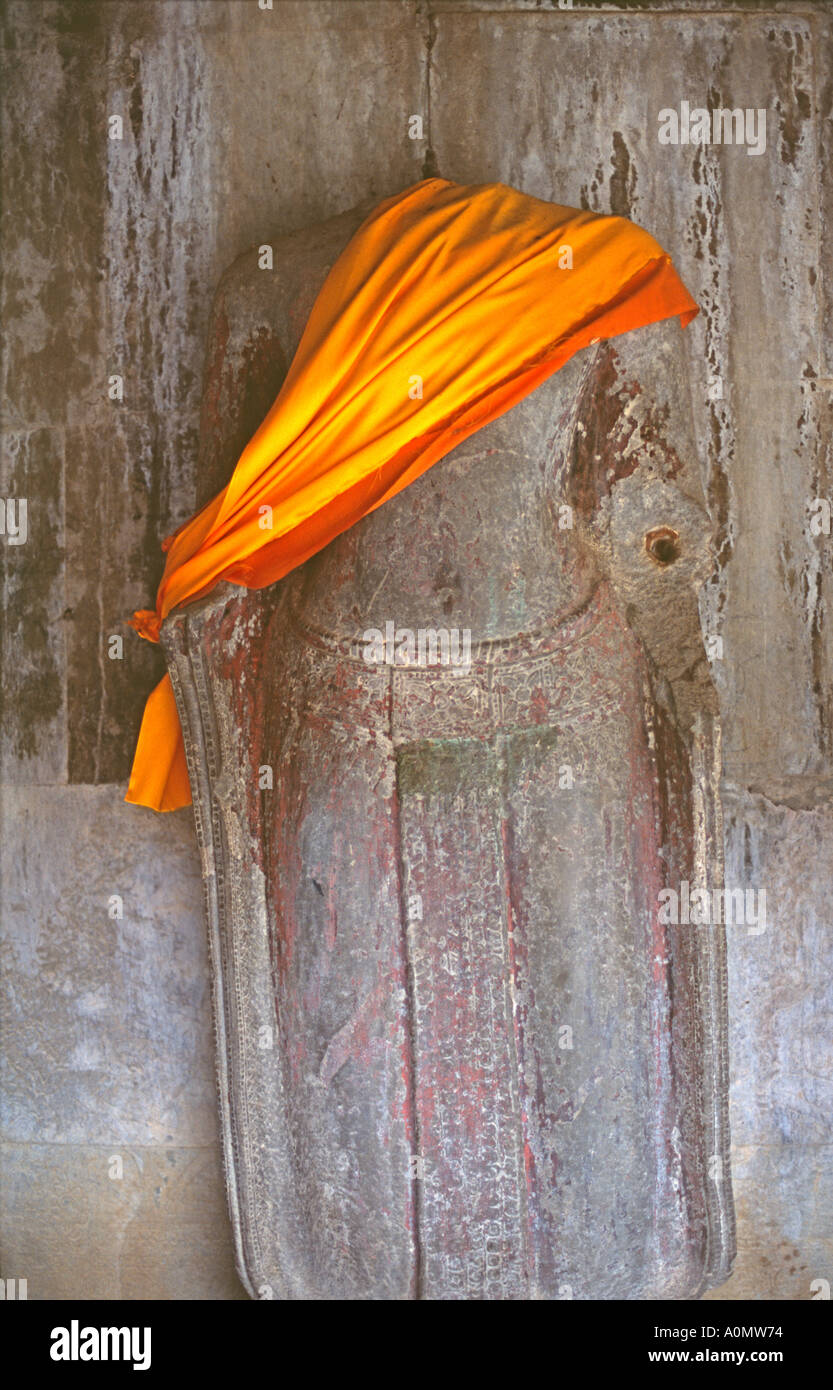 A sash is placed upon a desecrated Buddha statue at Angkor Wat Cambodia - Stock Image