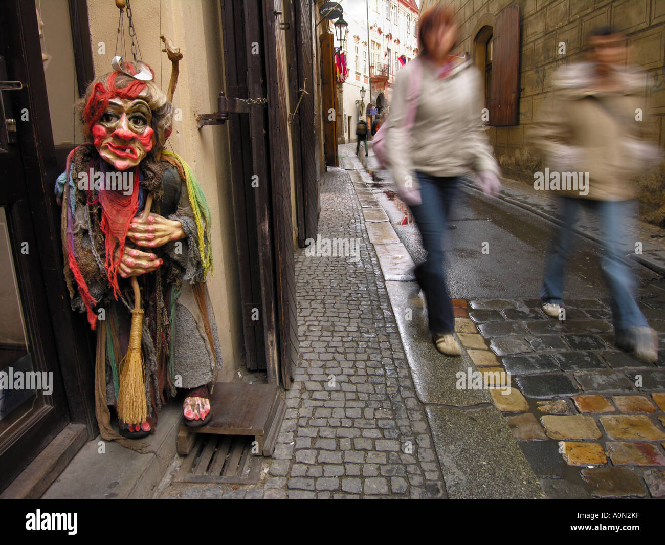A Halloween puppet in for form of a witch, in a shop doorway in a cobbled street in Prague, Czech Republic. - Stock Image