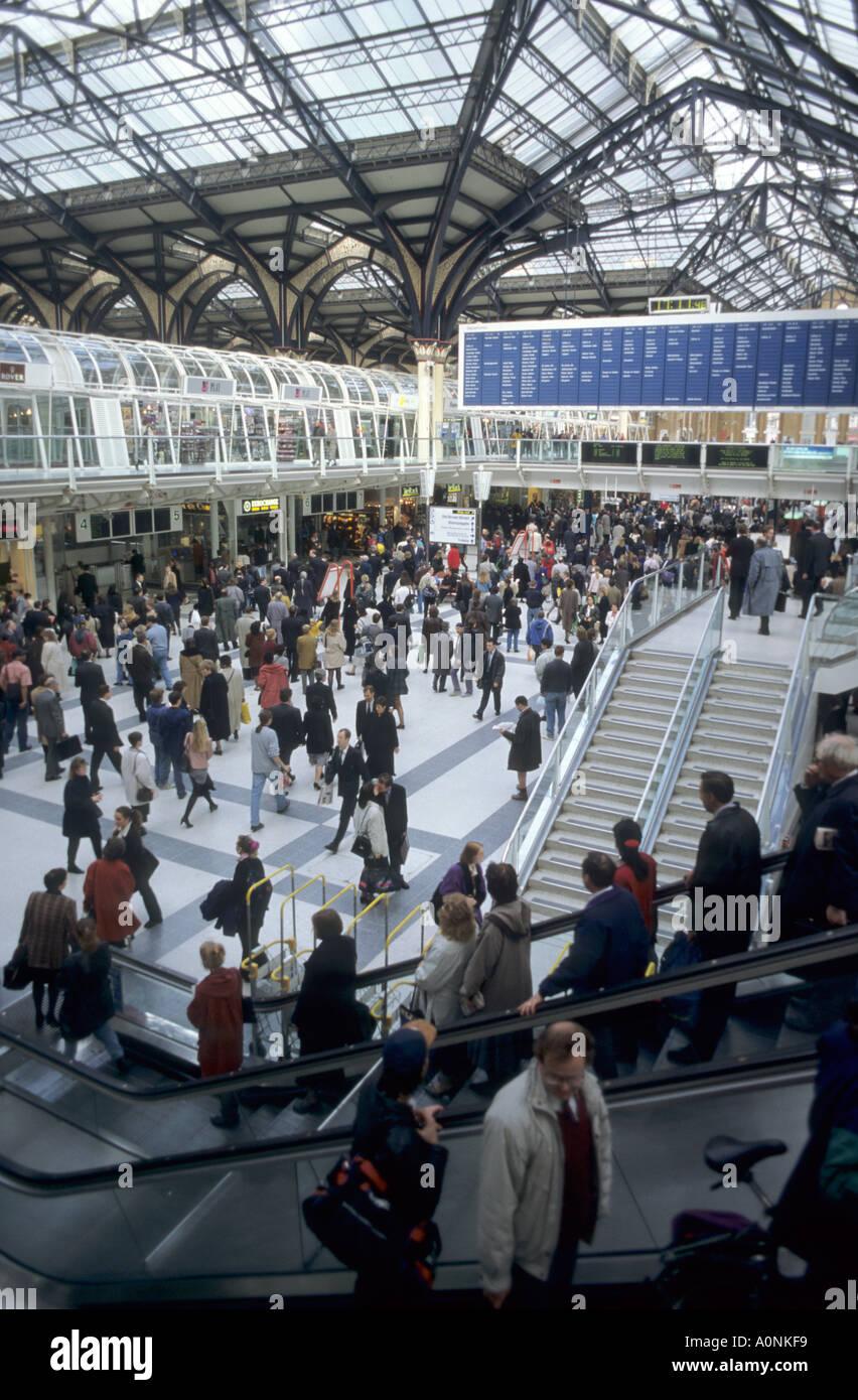 London, England. Crowd of people on Liverpool Street station; escalators; signs. - Stock Image
