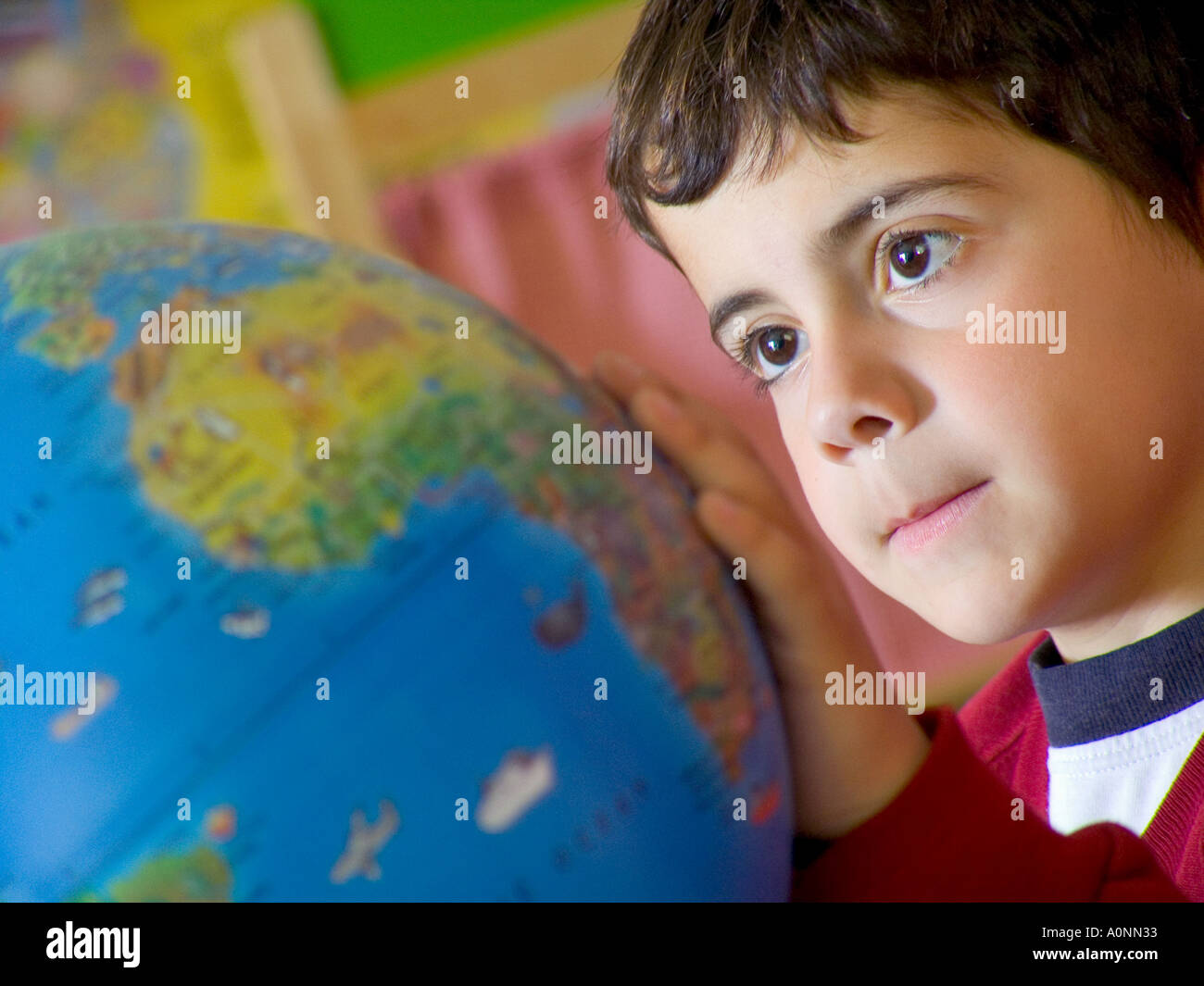 Close view on infant boy in school kindergarten class looking at world atlas globe - Stock Image