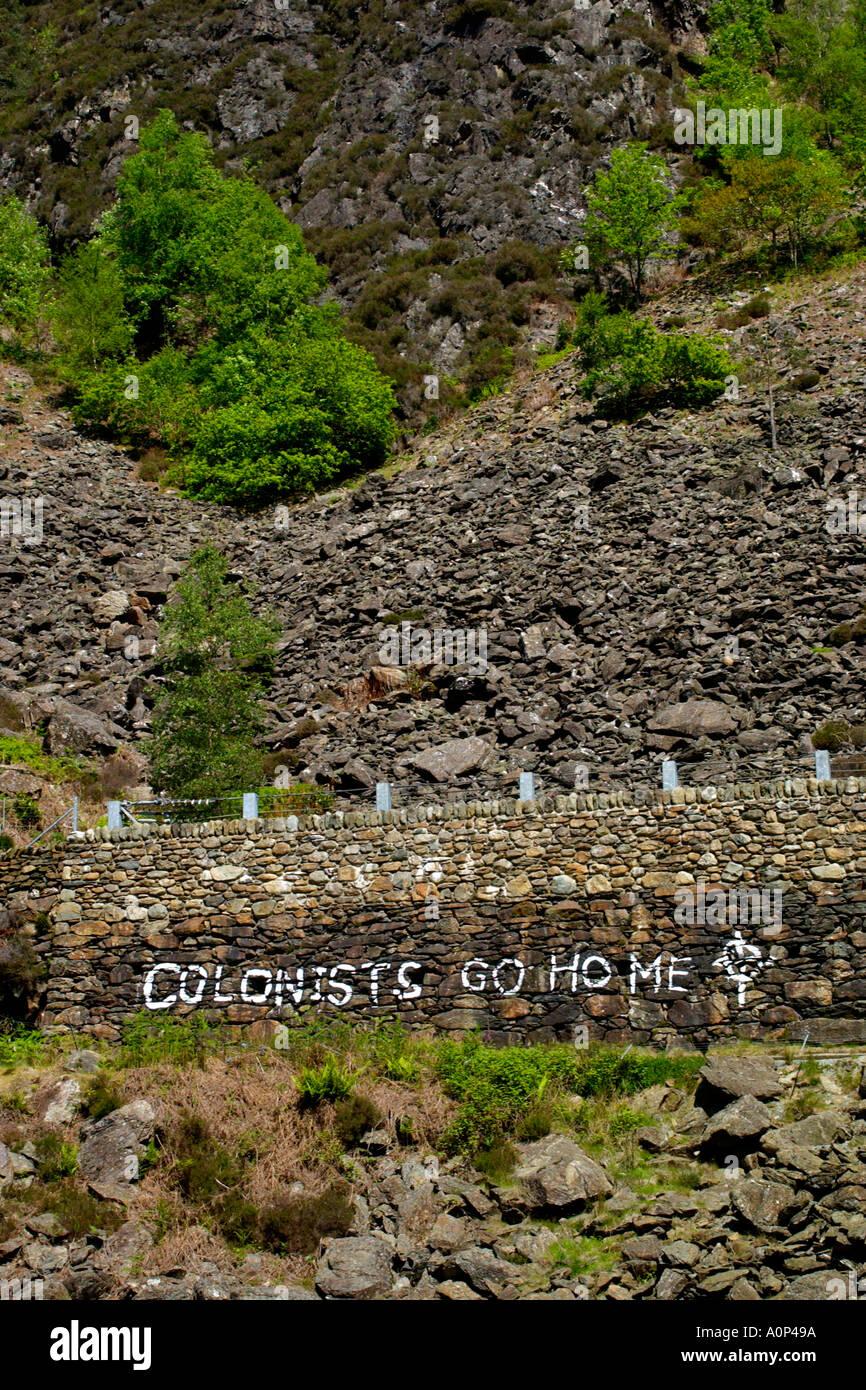 COLONISTS GO HOME Welsh extremist grafitti on roadside stone wall near Beddgelert Gwynedd North Wales UK - Stock Image