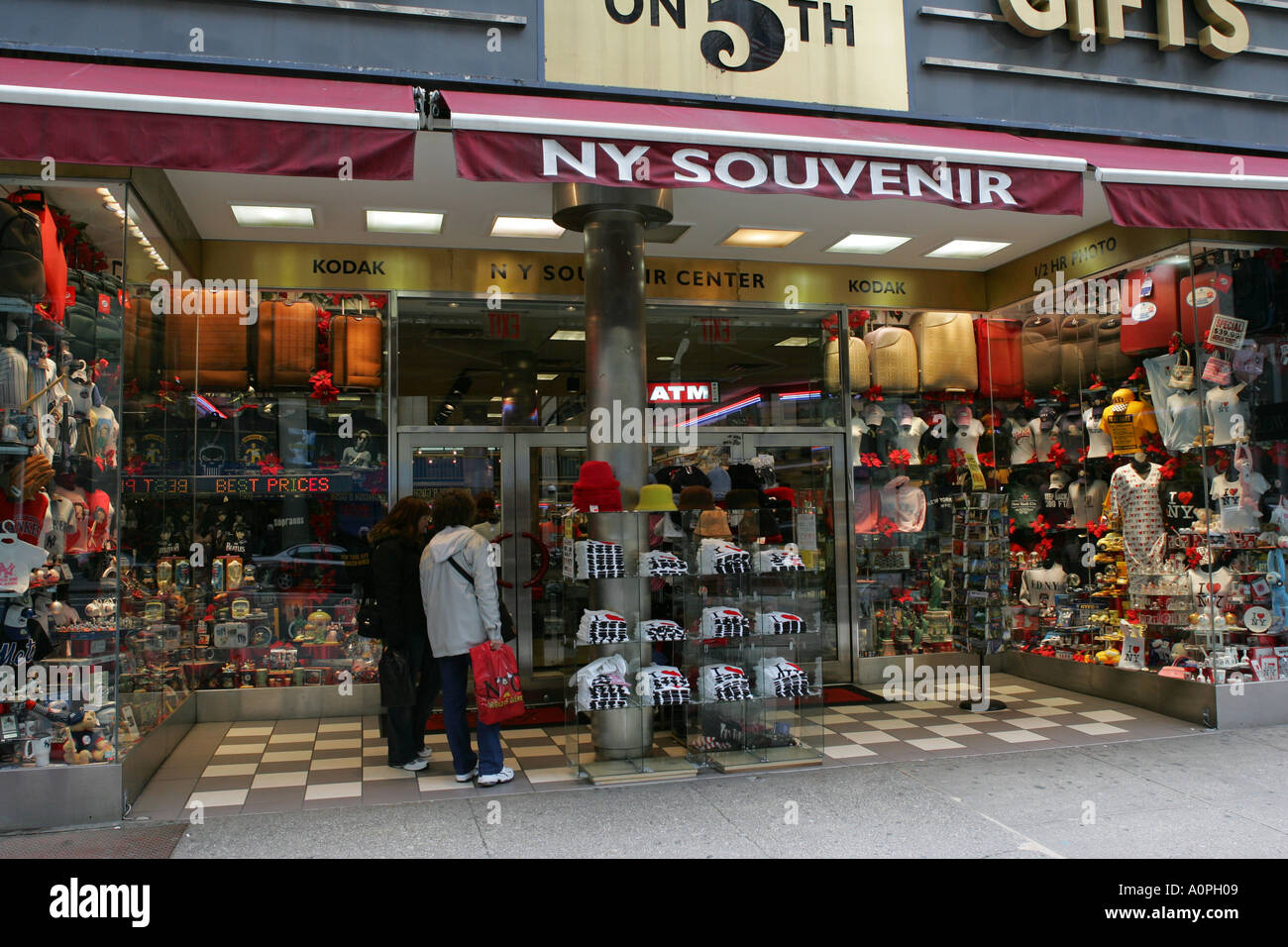 Tourists browse the cheap low cost goods in a 5th fifth Avenue souvenir shop store New York City America USA - Stock Image