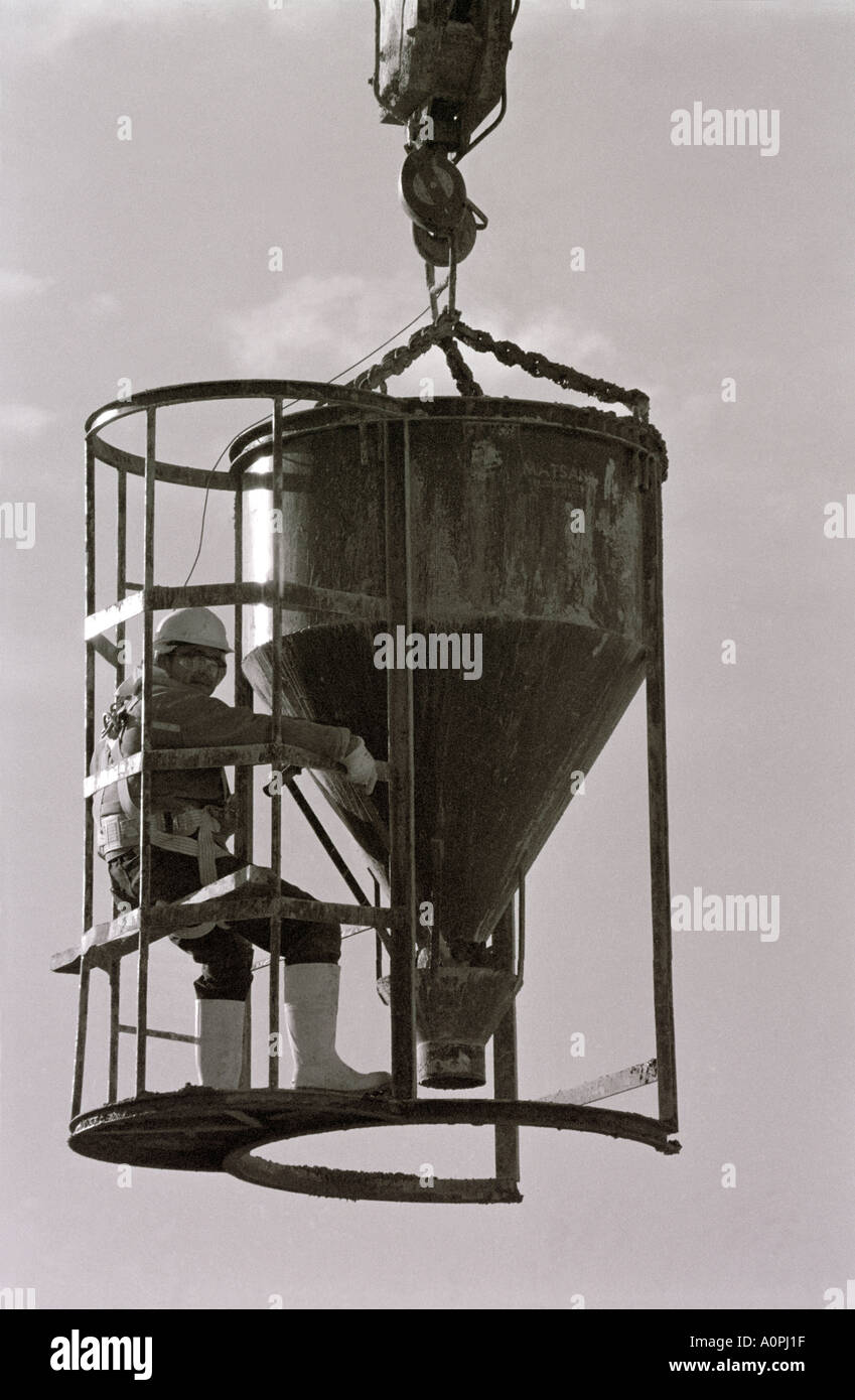 Concrete Bucket With Its Operator Suspended On End Of Crane