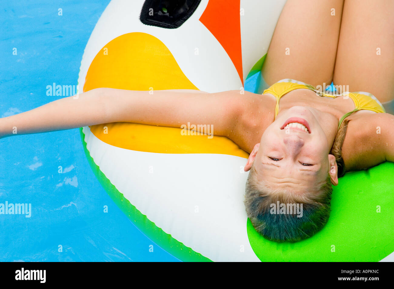 Smiling Girl lounging in pool Stock Photo
