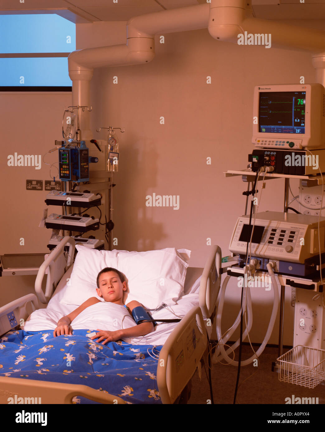 Hospital. Paediatrics. Young boy patient in Intensive care ward bed. - Stock Image