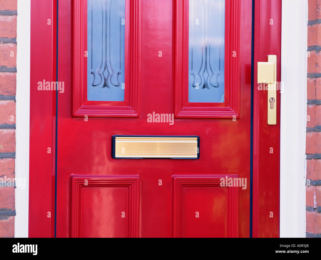 Architecture. Residential house. Glazed, red front door with letter box and lock. - Stock Image