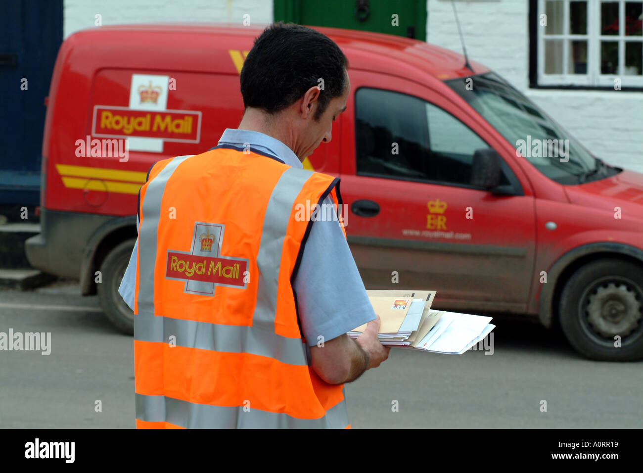 postman delivers letters in rural location England UK Royal Mail - Stock Image