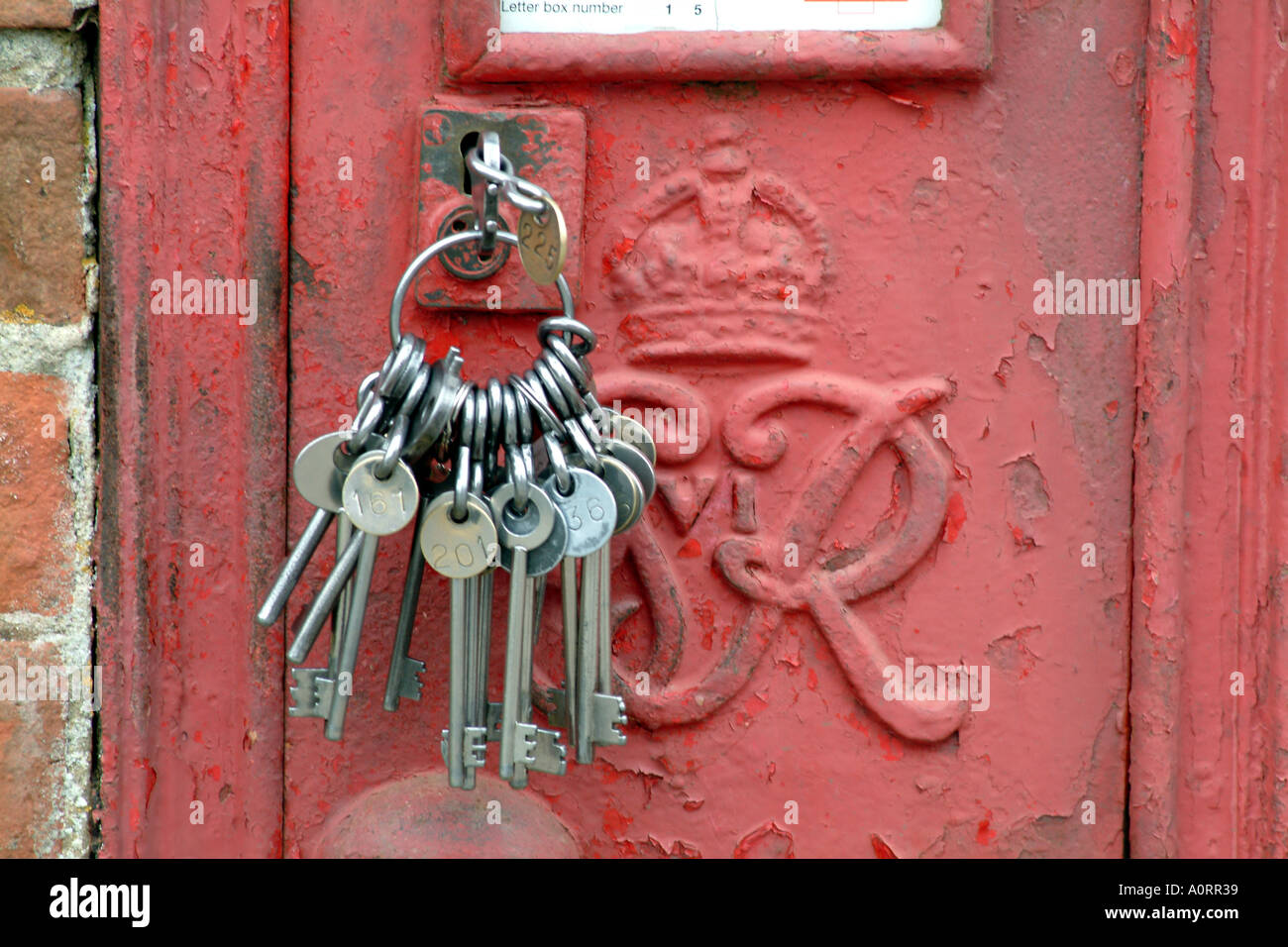 red english royal mail letter box with keys in lock open close