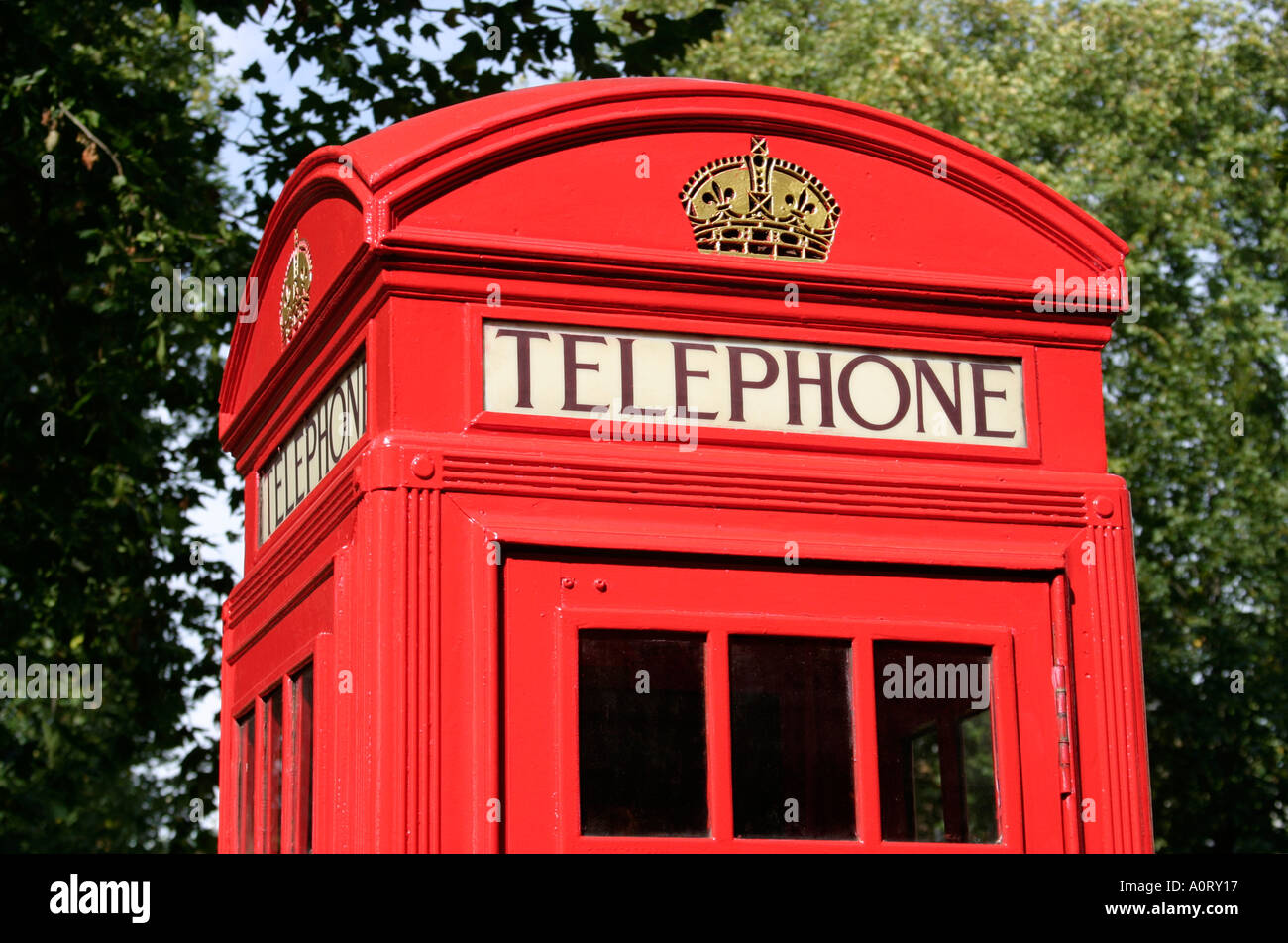 The top of a bright red phone box or booth in England with the word TELEPHONE in large black text - Stock Image