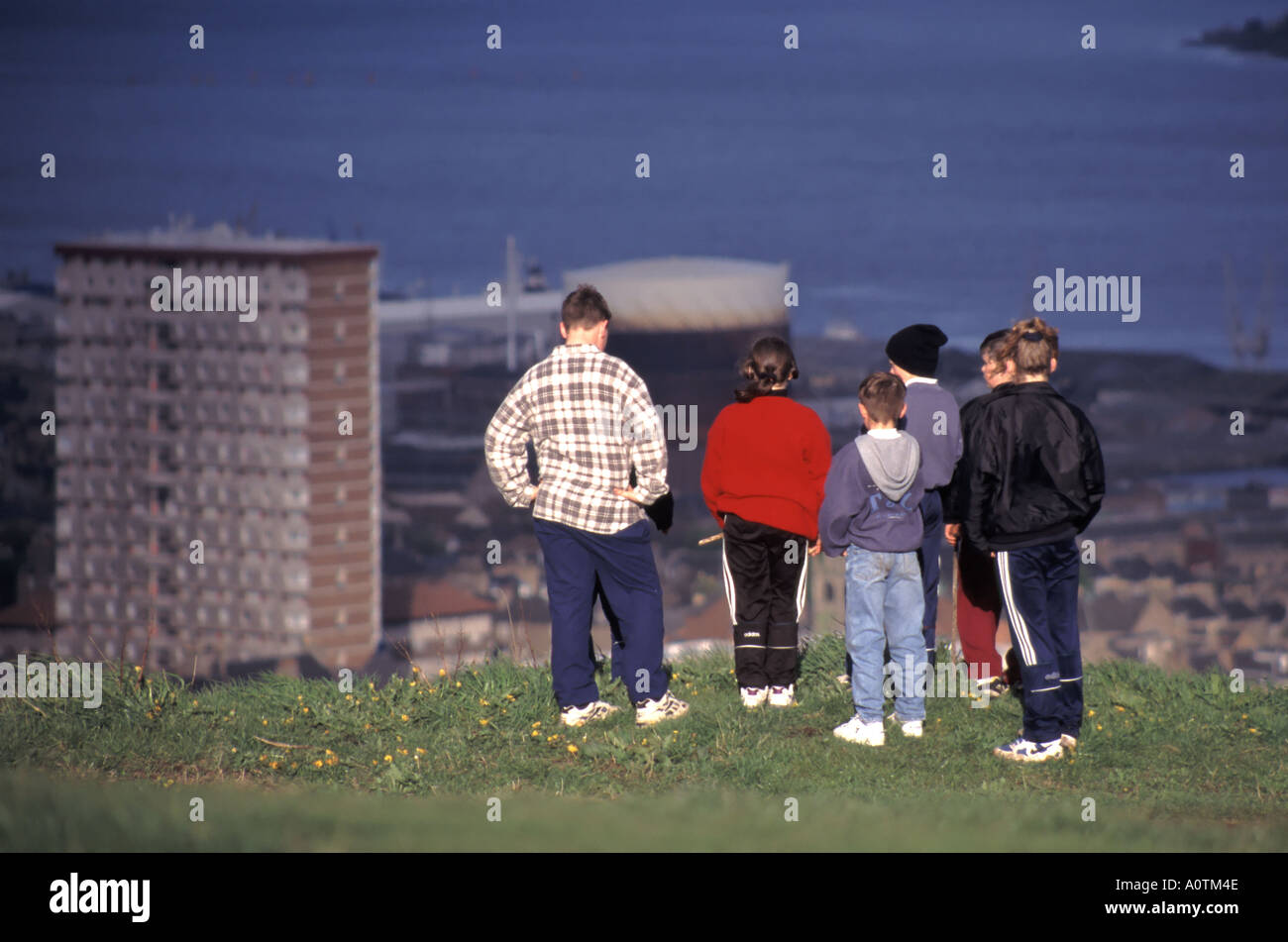Dundee youngsters looking down on urban areas including high rise flats from highpoint known as Dundee Law - Stock Image