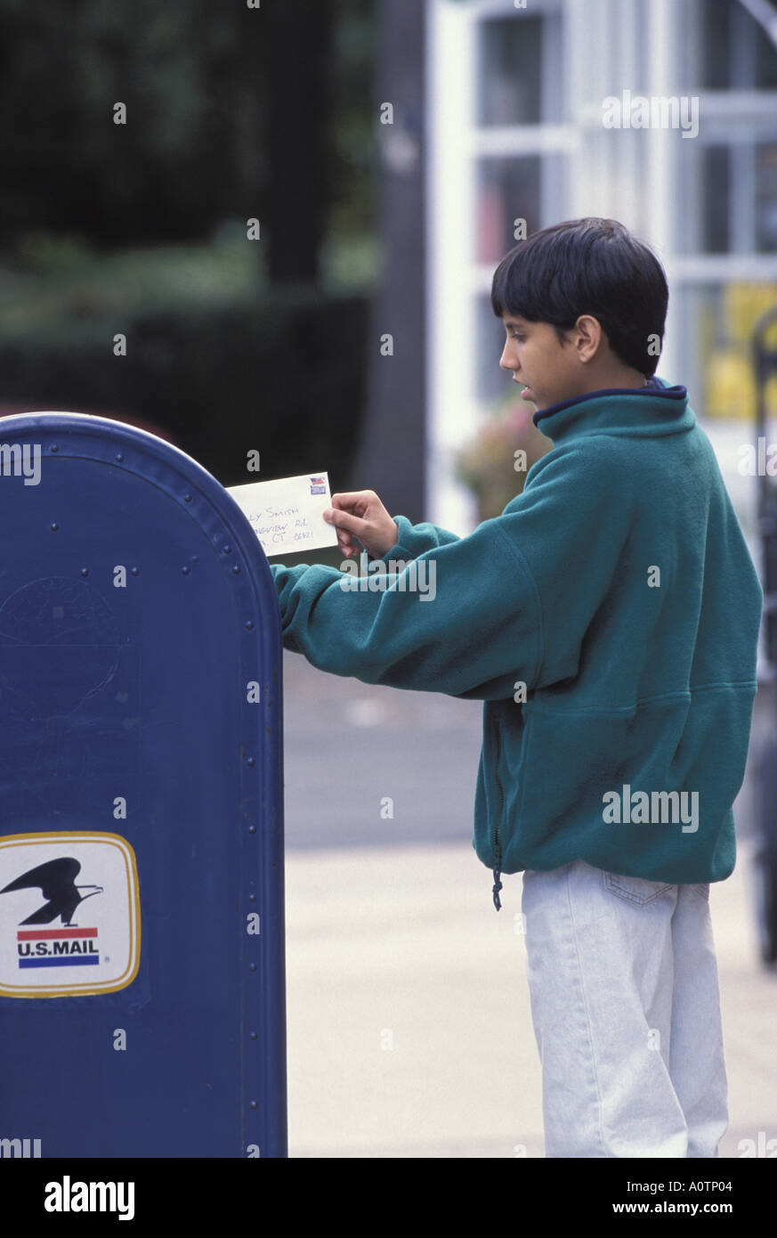 Asian American Boy Mailing Letter In Mailbox Stock Photo