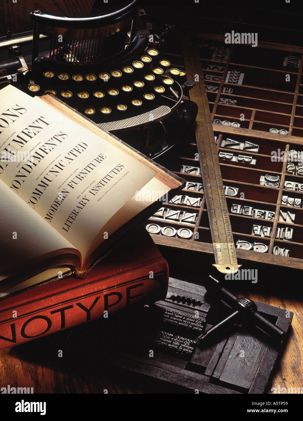 Still life of an antique typewriter along with typesetters tools and metal type - Stock Image