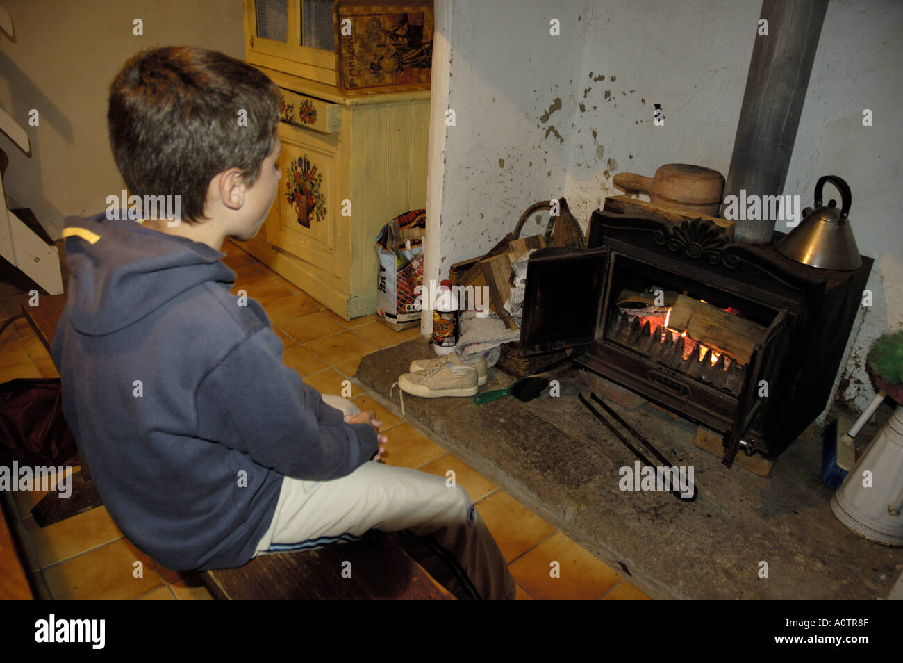 Ten years old boy looking at the fire - Stock Image