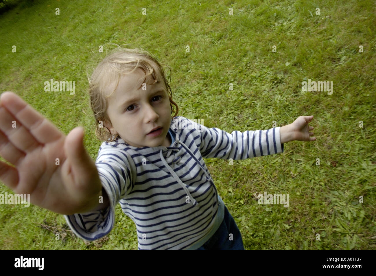 Little girl with wet hair gesturing towards the camera. Stock Photo