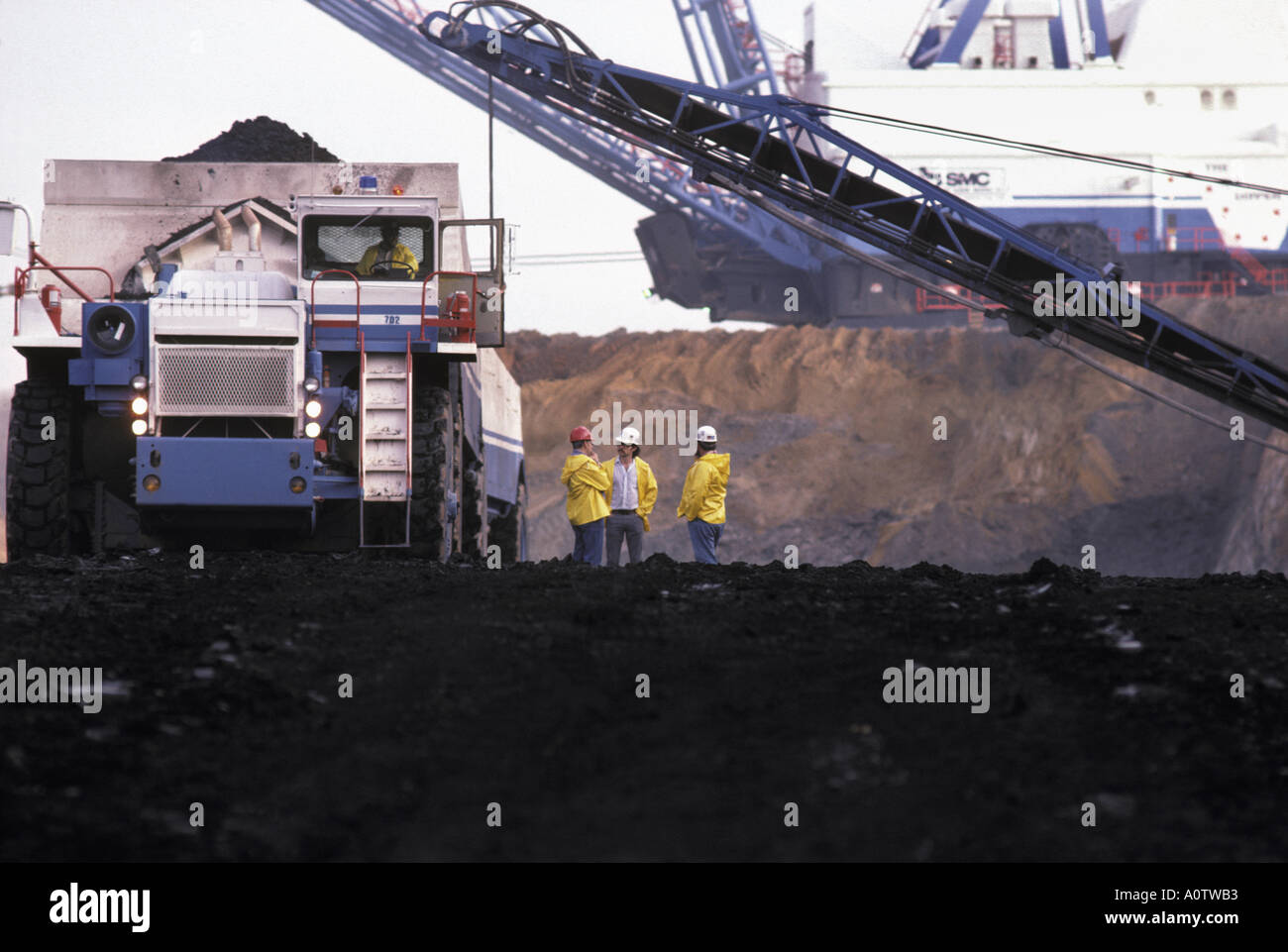 Huge coal haul truck and enormous electric dragline shovel and conveyor at a Texas open pit coal mine, dwarfing Stock Photo