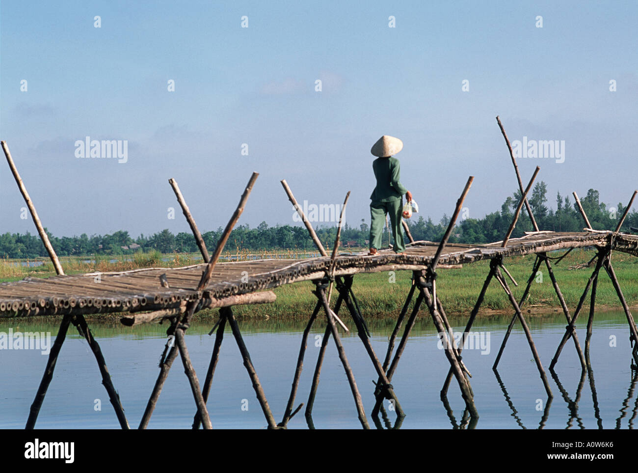 Vietnamese woman in typical conical hat strolling across a bamboo footbridge that spans the Thu Bon River Hoi An Vietnam - Stock Image