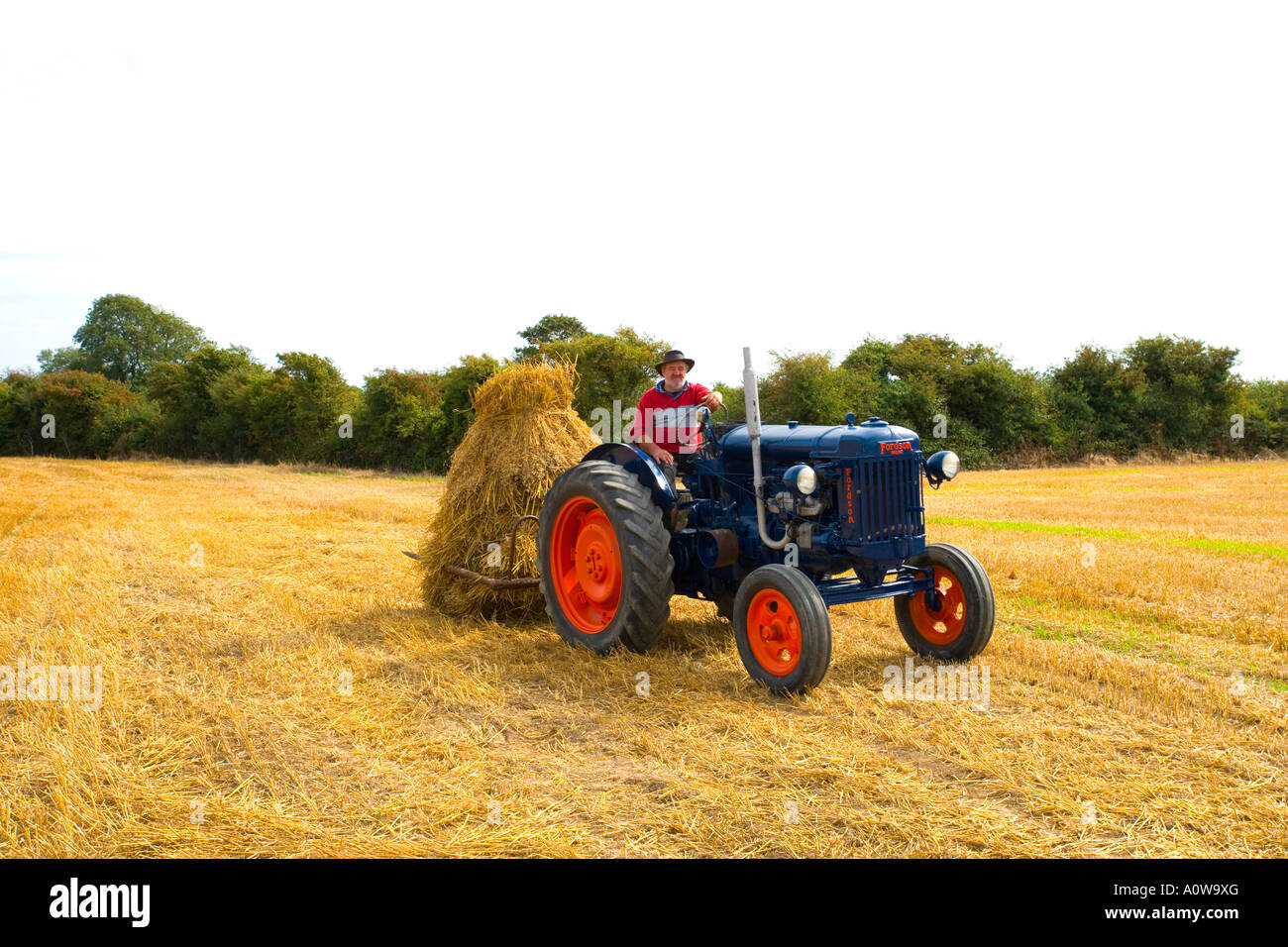 farmer saving the hay with his tractor in the field - Stock Image