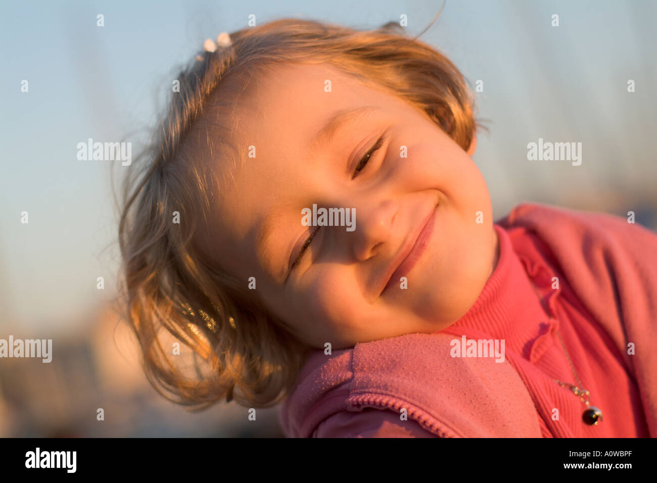 Portrait of a smiling little girl at sunset, France. Stock Photo