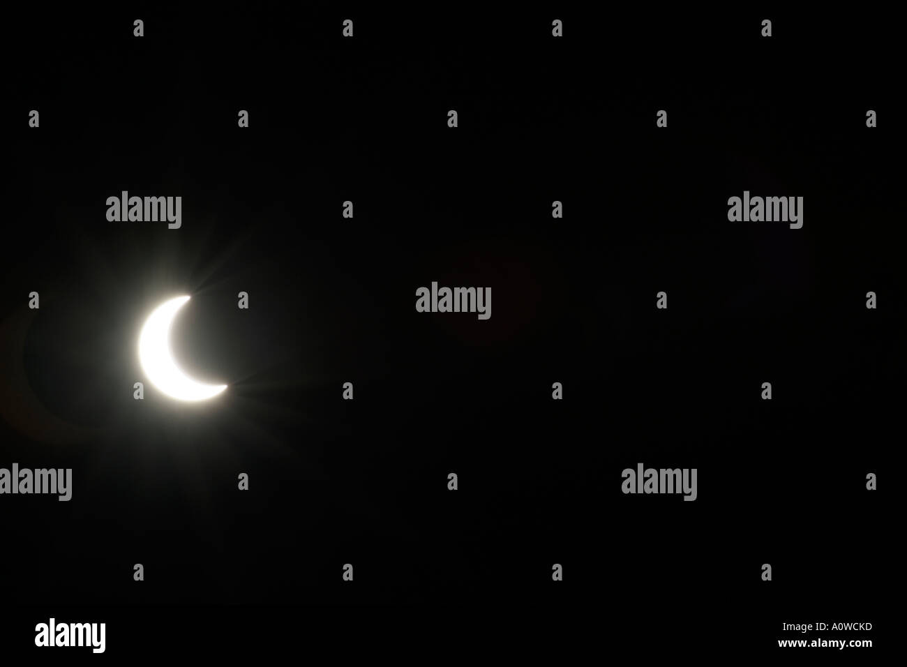 Solar eclipse / half or crescent moon in the night sky. - Stock Image