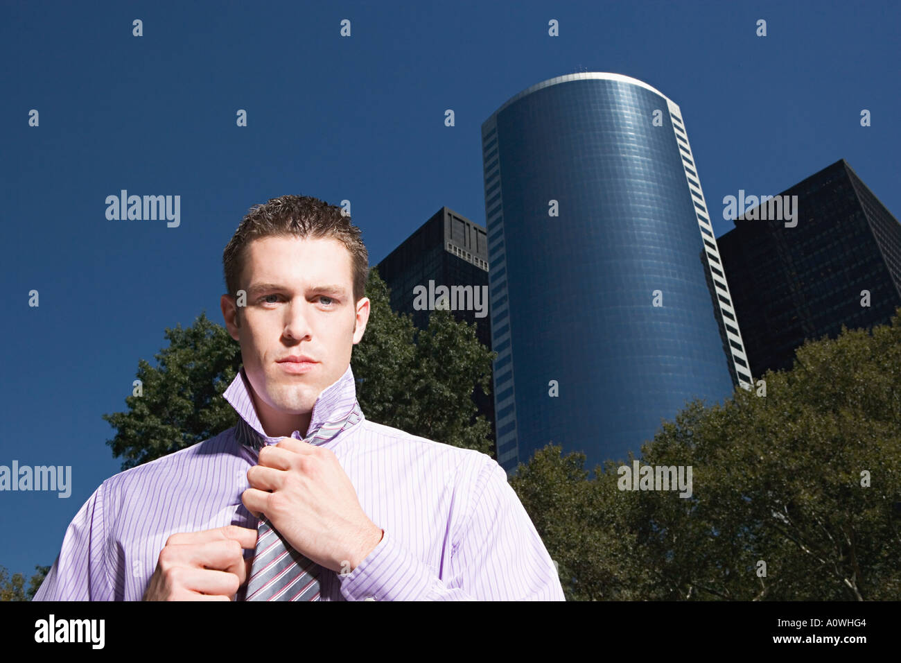 Male office worker adjusting necktie - Stock Image