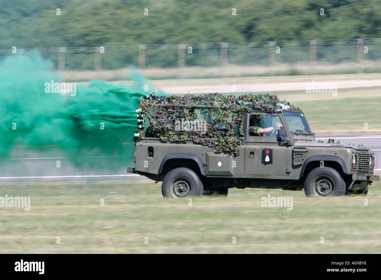 British Army landrover speeds off trailing green smoke as part of military TAC demo demonstration RIAT 2005 RAF Fairford - Stock Image