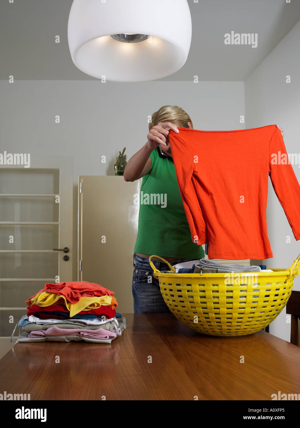 Woman folding clothes whilst on mobile phone - Stock Image