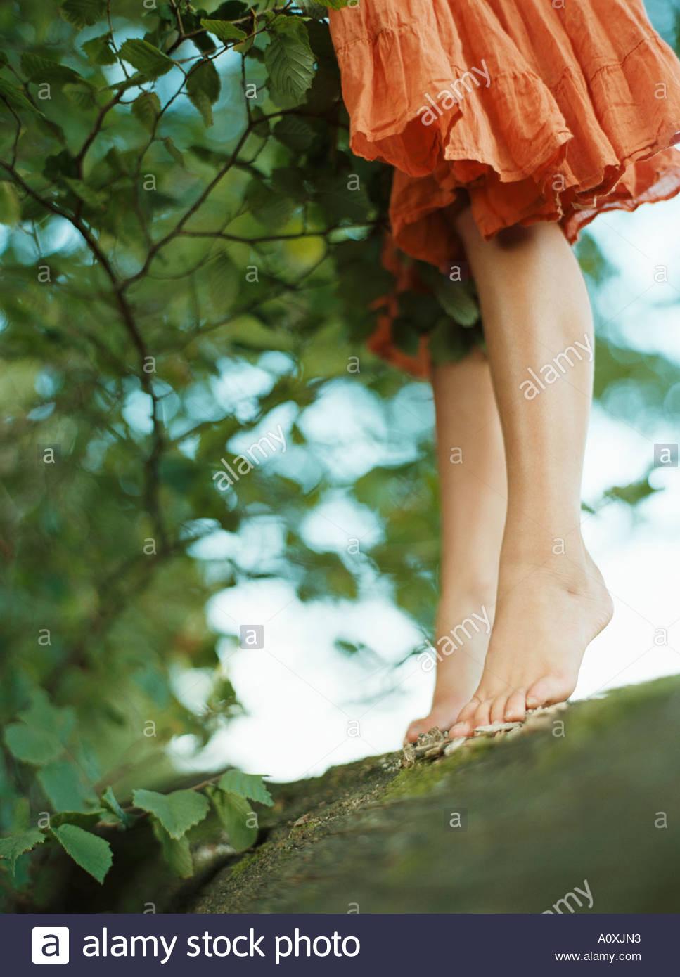 Girl standing barefoot on a log - Stock Image