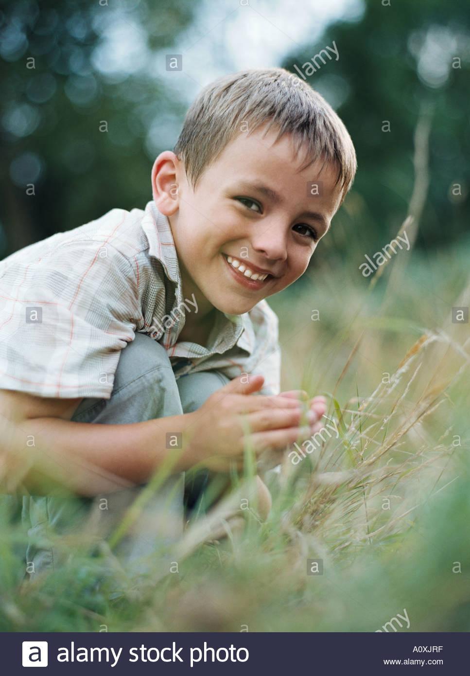 Boy crouching in grass Stock Photo