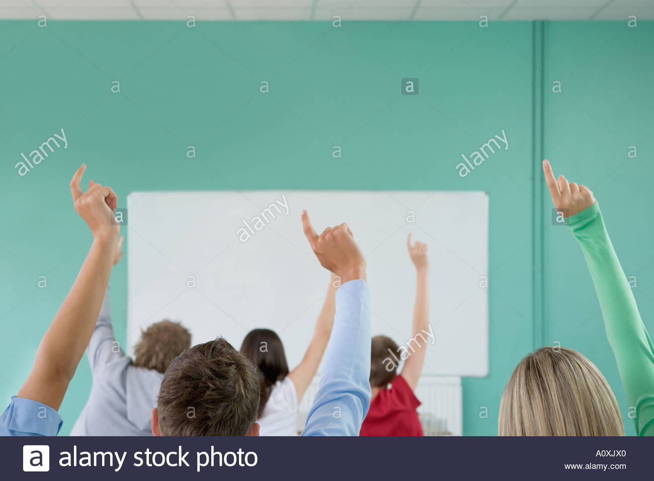 School students raising their hands - Stock Image