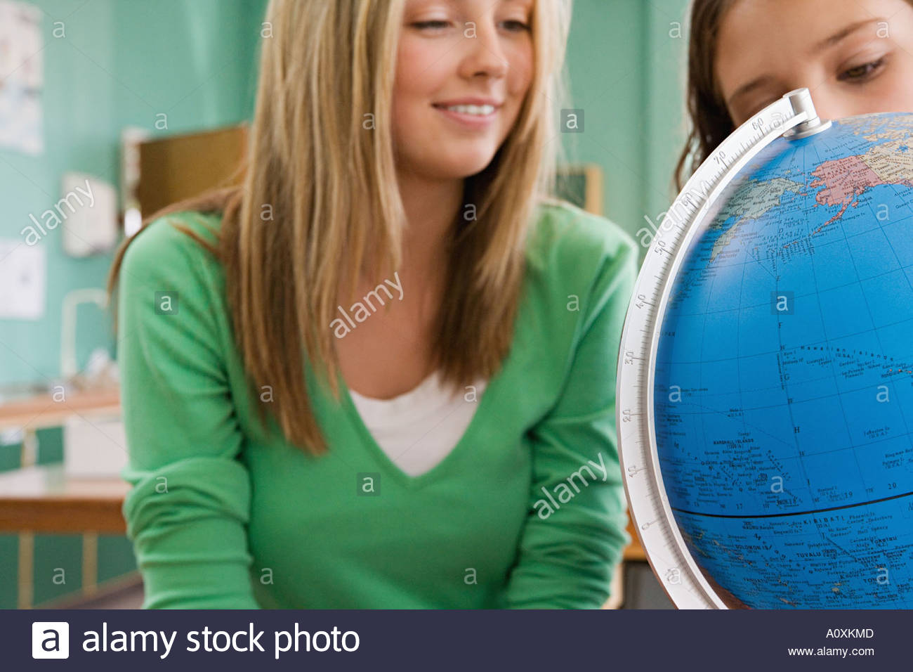 Girls looking at a globe - Stock Image