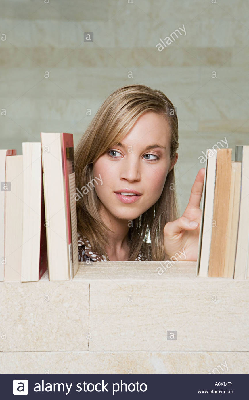 Woman looking at books - Stock Image