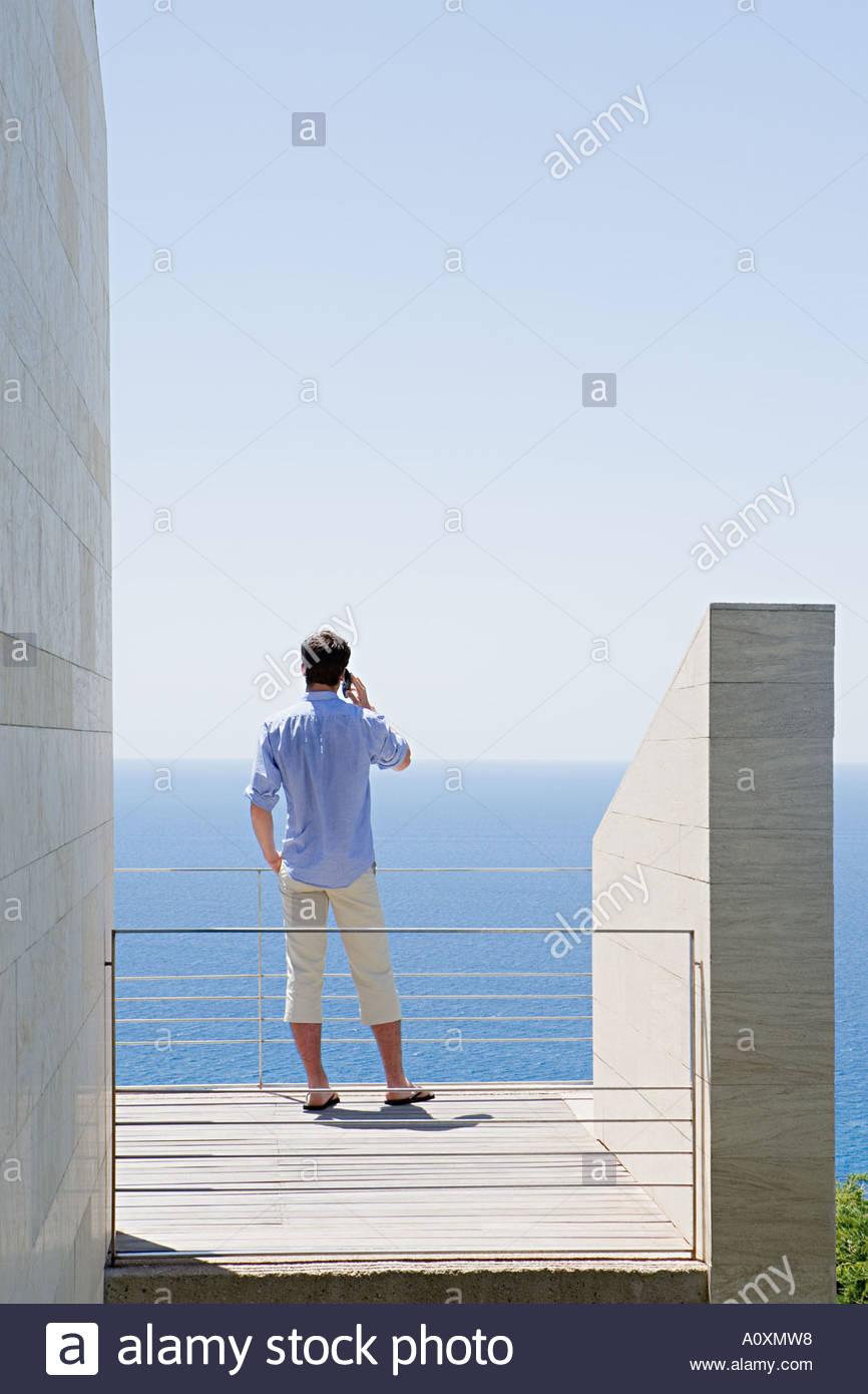 Man on balcony using mobile phone - Stock Image