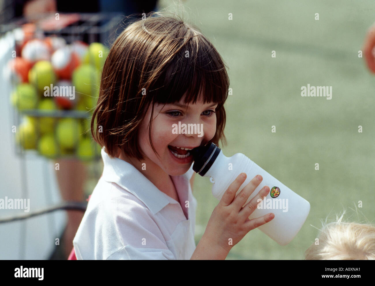 five year old girl drinks from water bottle at tennis court Kingston Upon Thames nr London UK england britain europe eu - Stock Image