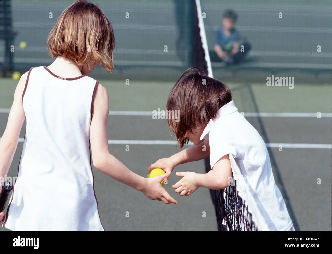 five and seven year old girls enjoy lesson at tennis court Kingston Upon Thames nr London UK england britain europe eu - Stock Image