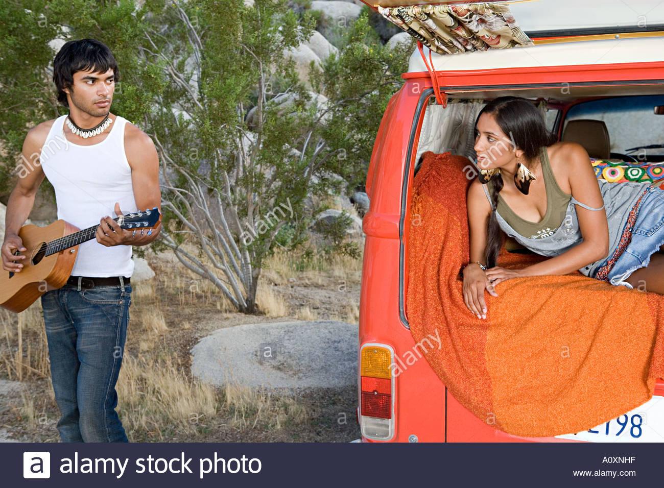 Man playing guitar to girlfriend - Stock Image