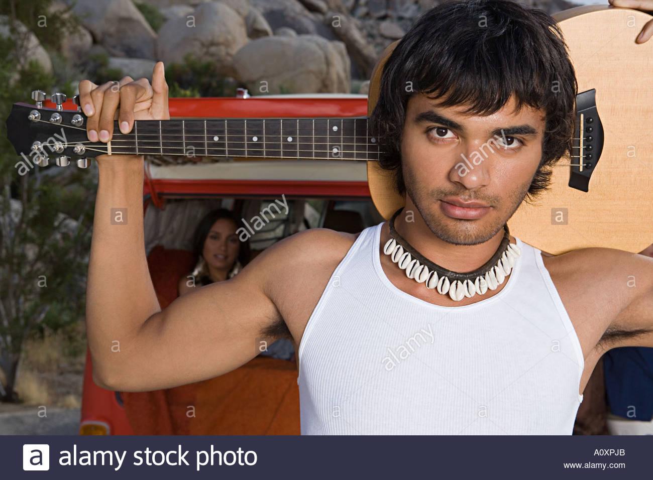 Young man carrying guitar - Stock Image