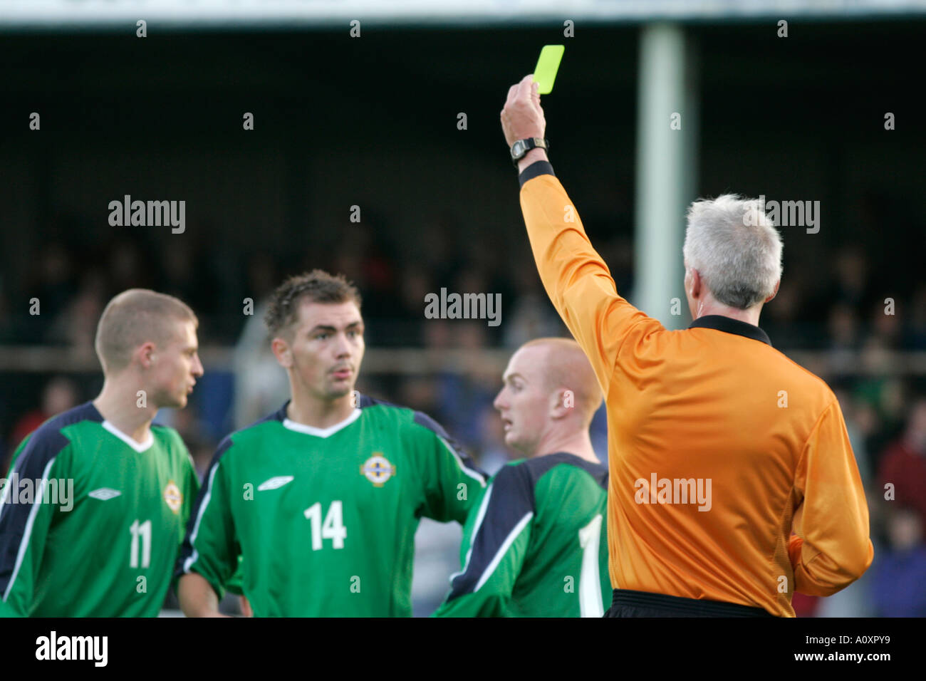 The referee hands out a yellow caution card to northern ireland players Northern Ireland v USA Northern Ireland Milk Cup - Stock Image