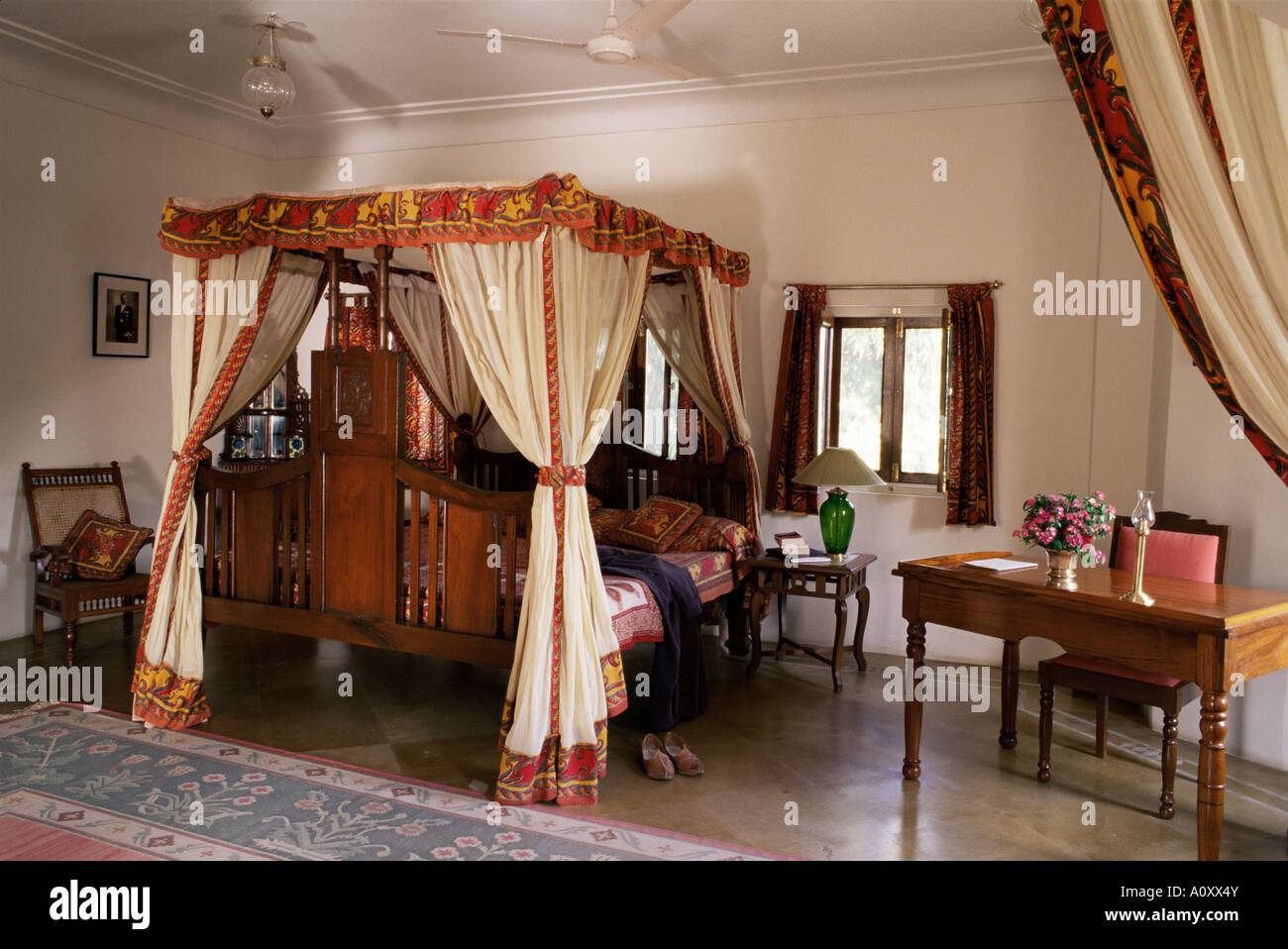 Reproduction colonial style four poster bed and block printed fabrics in guest bedroom Samode Haveli Gangapol District - Stock Image