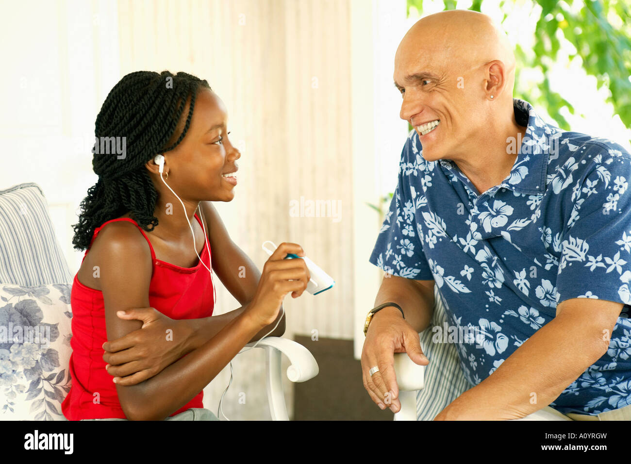 Young African Girl Talking To Older Caucasian Man Stock Photo