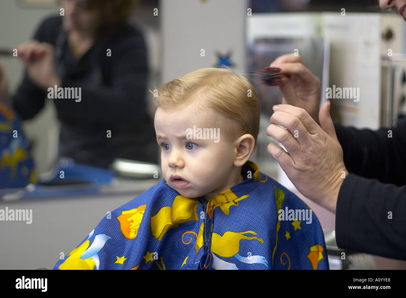 haircut for 1 year old boy one year boy sits in barber stool for haircut 4204 | one year old boy sits in barber stool for first haircut toddler is A0YYE8
