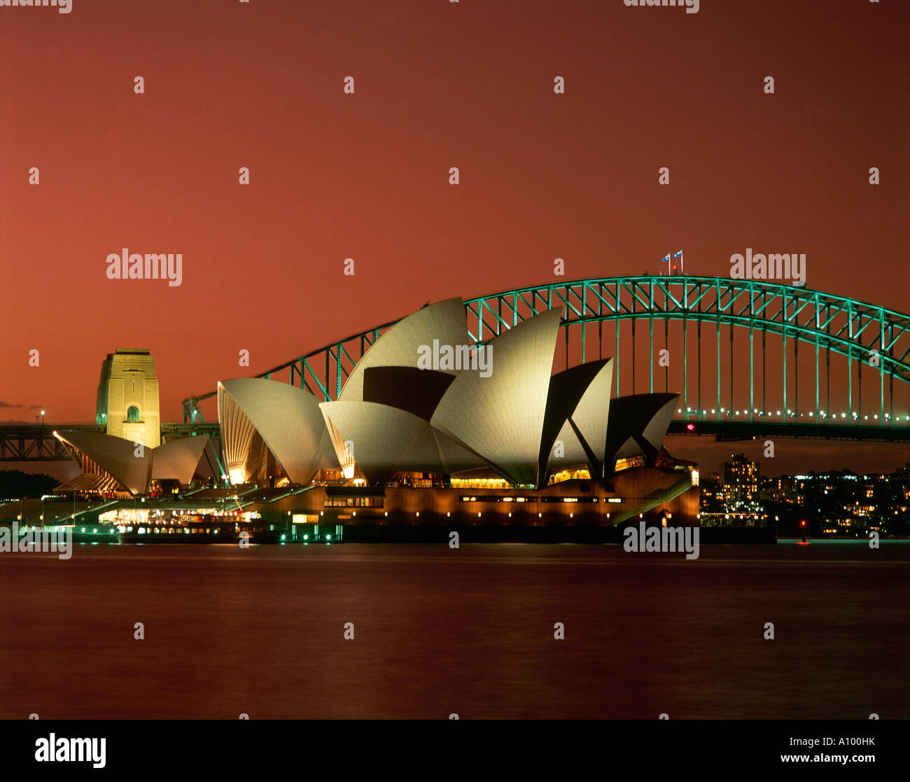 View of the Sydney Opera House designed by Jorn Utzon 1956 completed 1972 and Harbour Bridge illuminated at night - Stock Image